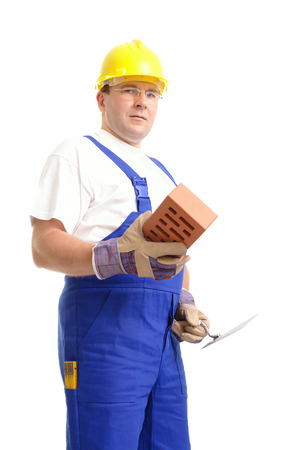 overall: Construction worker wearing blue overall and yellow helmet holding stainless steel trowel and brick over white background