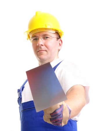 an erection: Construction worker wearing blue overall and yellow helmet holding stainless steel trowel over white background