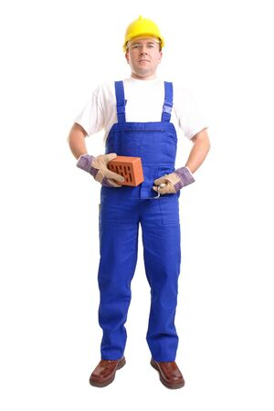 Construction worker wearing blue jumpsuit and yellow helmet posing with stainless steel trowel and brick over white background Stock Photo - 1407020