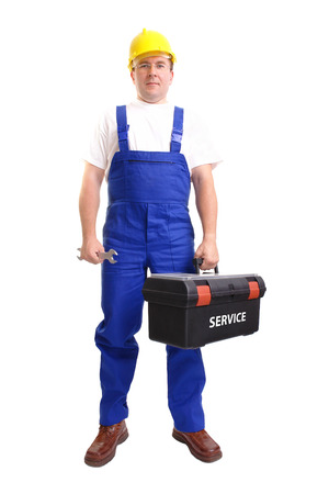 Serviceman wearing yellow helmet and blue overall holding black toolbox in one hand and flat wrench in another hand over white background