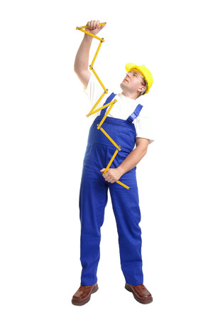 unfold: Builder wearing blue jumpsuit and yellow helmet unfolding wooden ruler standing over white background Stock Photo