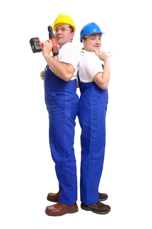 borer: Serviceman and servicewoman wearing yellow and blue helmet and blue overall facing their backs to each other - man holding borer - woman holding flat wrench - isolated on white background Stock Photo