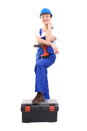 overall: Service woman wearing blue helmet and overall with drilling machine posing with one foot resting on toolbox over white Stock Photo