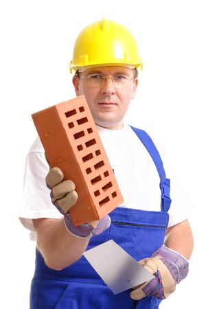 Construction worker wearing blue jumpsuit and yellow helmet holding stainless steel trowel and brick over white background Stock Photo - 1416328