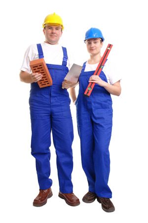 spirit level: Male and female builders wearing yellow and blue helmet and blue overall - man holding brick and stainless steel trowel - woman holding spirit level - isolated on white background