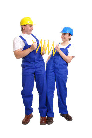 Builder couple wearing yellow and blue helmet and jumpsuit unfolding wooden ruler over white background