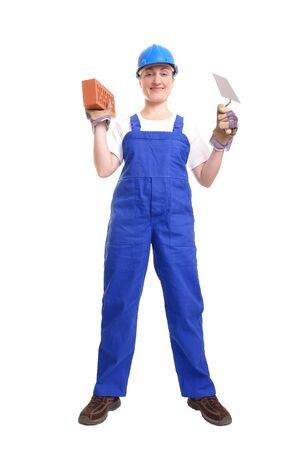Female construction worker wearing blue jumpsuit and helmet holding stainless steel trowel and brick over white background Stock Photo - 1416322