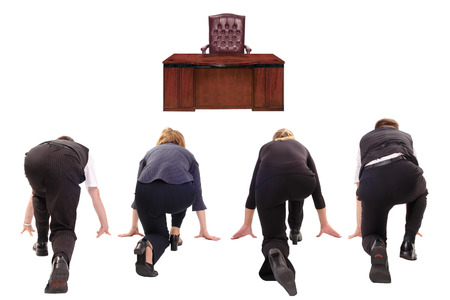 Four business people lined up in race to win boss chair - rat race concept photo