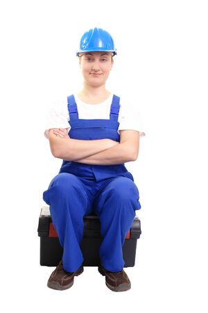 Service woman wearing blue helmet and overall sitting cross-armed on black toolbox over white photo