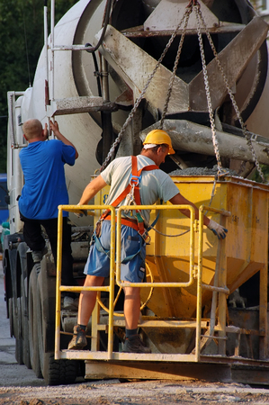 Construction workers pouring concrete mix from truck concrete mixer into yellow charging hopper
