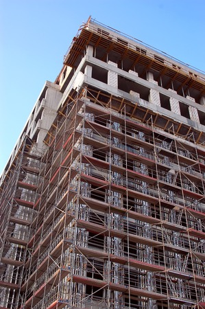 erection: Closeup of raw concrete residential building surrounded by scaffolding Stock Photo