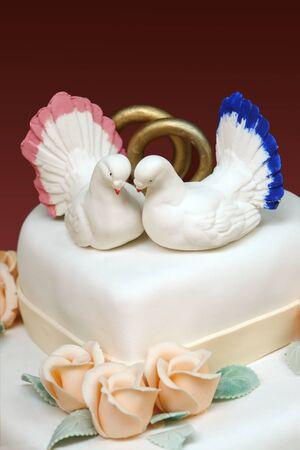 Closeup of white iced wedding cake with two white doves and wedding rings decoration on top photo