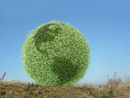 Green globe with american continents resting in grass over clear blue sky Stock Photo
