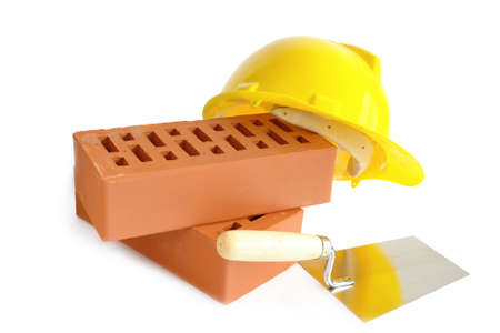 Two perforated bricks, stainless steel trowel and yellow hard hat over white background Stock Photo - 1615077