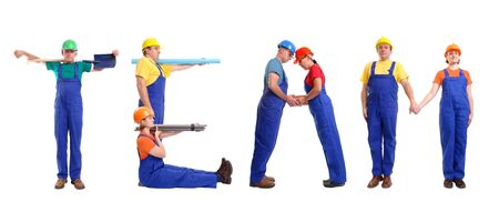 Group of young people wearing different color uniforms and hard hats forming Team word - isolated on white background photo