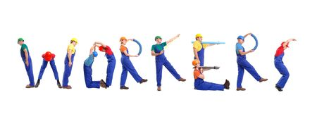 Group of young people wearing different color uniforms and hard hats forming Workers word - isolated on white background Stock Photo
