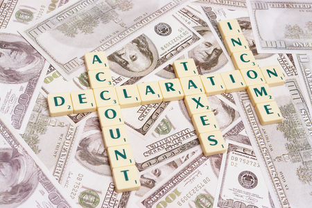 declaration: Cubes spelling declaration, account, taxes, income - placed over US one hundred dollar bills Stock Photo