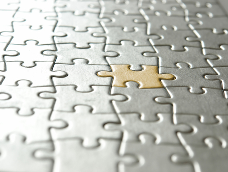 mismatch: Background of silver puzzle pieces and one golden piece - selective focus Stock Photo
