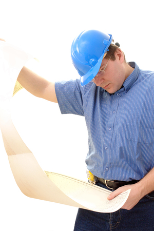 Civil engineer wearing blue helmet studying a building plan over white photo