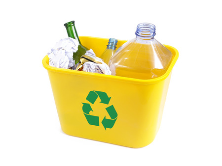 Yellow plastic garbade bin with green recycle symbol containing empty plastic bottles, beer cans, paper and color glass bottle over white background