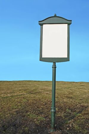 Blank green metal signpost in the grass over blue sky photo