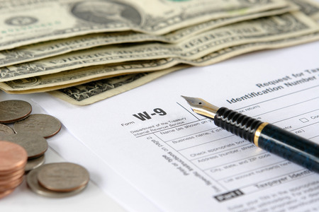 W-9 income tax form with pen and american dollars Stock Photo - 1717651