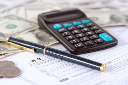 podatnika: Puste W-9 podatku dochodowego w formie pióro, kalkulator i dolary amerykańskie