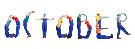 Group of young people wearing different color uniforms and hard hats forming October word - isolated on white background - calendar concept photo