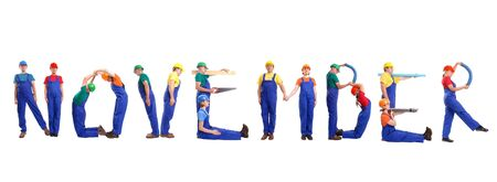 Group of young people wearing different color uniforms and hard hats forming November word - isolated on white background - calendar concept photo