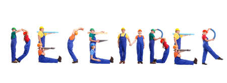 Group of young people wearing different color uniforms and hard hats forming December word - isolated on white background - calendar concept photo