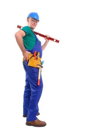spirit level: Builder wearing blue jumpsuit, helmet and toolbelt posing with spirit level over white background Stock Photo