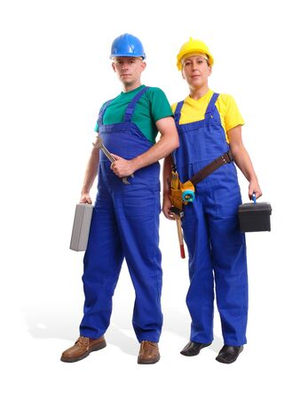 overall: Serviceman and servicewoman wearing blue and yellow helmet and overall each holding toolboxes - isolated on white background