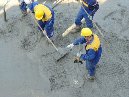 Construction workers spreading freshly poured concrete mix at the building site Stock Photo