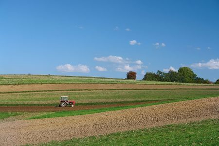 cropland: Farm tractor plowing arable field