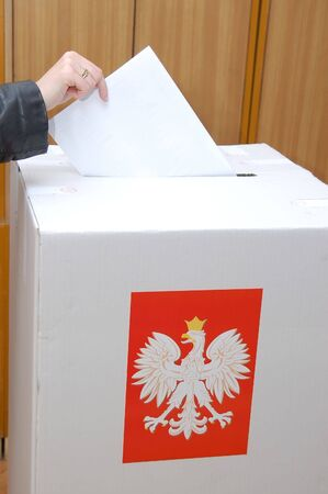 Voter casting vote into ballot box in Parliamentary election in Poland Stock Photo - 1942167