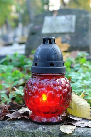 votive candle: Red votive candle lit on old tombstone