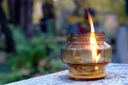 Glass votive candle lit on tombstone Stock Photo - 1978808