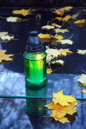 votive candle: Green votive candle lit on black marble tombstone covered by dead maple leaves