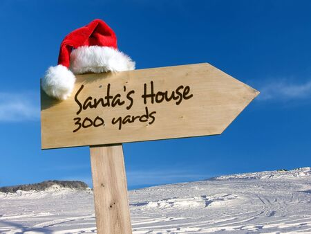 Wooden signpost with Santas hat indicating Santas House with snow and blue sky in the background Stock Photo