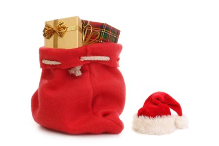 sack background: Red Santa Claus hat and bag full of christmas presents over white background
