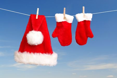 Red santa claus hat and pair of gloves drying in the open air hanging on clothes line affixed with wooden pegs
