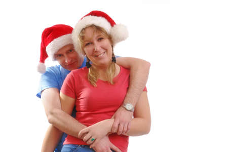 Young happy couple wearing red santa hats posing over white background Stock Photo - 2037505