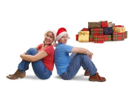 Young happy couple wearing red santa hats sitting on floor back-to-back with pile of christmas present in the background Stock Photo - 2037507