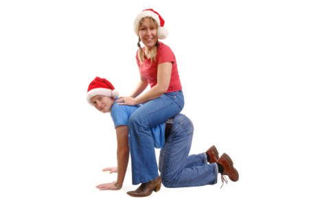 Young happy couple wearing red santa hats playing piggy-back on floor over white background Stock Photo - 2046856