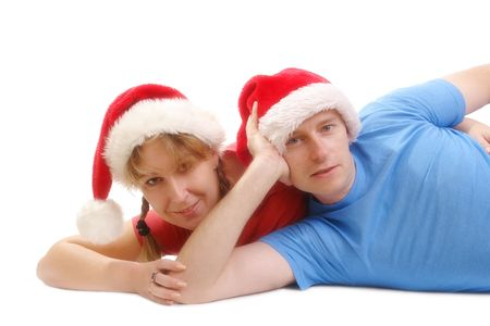 Young happy couple wearing red santa hats posing on floor over white background Stock Photo - 2046857