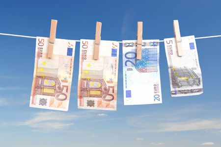Fifty, twenty and five euro banknotes hanging on laundry line attached with wooden clips over blue sky photo