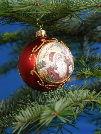 Red christmas ball with golden ornaments hanging on fir branch over blue background Stock Photo - 2087622