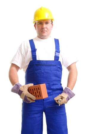 Construction worker wearing blue jumpsuit and yellow helmet holding stainless steel trowel and brick over white background