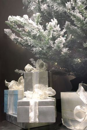 Closeup of christmas gifts stacked under christmas tree photo