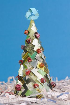 Ecological christmas tree made of newspaper cuttings with recycle three-arrow symbol on top over blue background Stock Photo